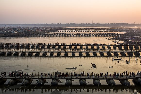 Pilgrims make their way over pontoon bridges near Sangam, the confluence of the holy rivers Ganga, Yamuna and the mythical Saraswati, during the Maha Kumbh Mela
