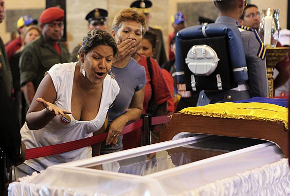 Supporters of the late Venezuelan President Hugo Chavez react as they view his coffin during a wake at the military academy in Caracas