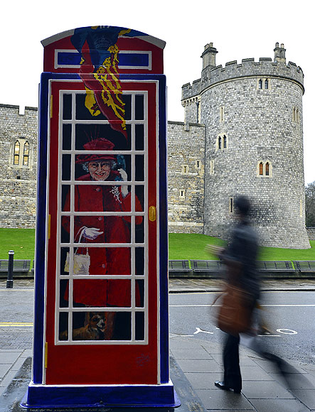 A pedestrian passes a painted image of Britain's Queen Elizabeth outside Windsor Castle in Windsor, southern England