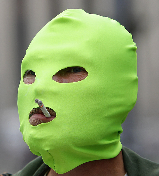 An protester wears a mask in support of members of a female punk band during a rally against Putin in Moscow