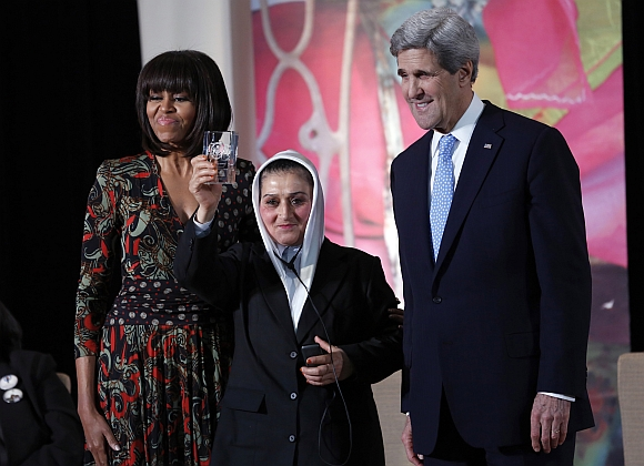 US First Lady Michelle Obama (left) and Secretary of State John Kerry (right) give Afghan First Sergeant Malalai Bahaduri the International Women of Courage Award at the state department in Washington
