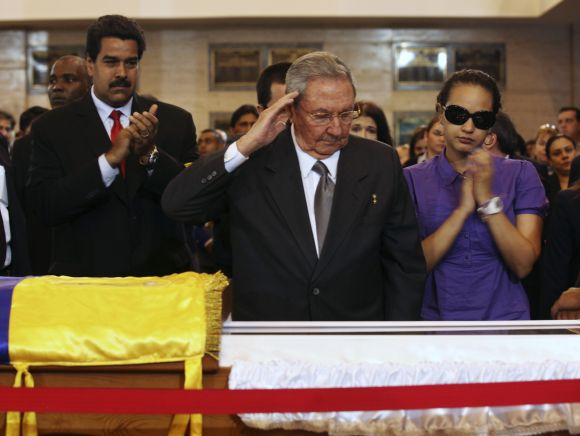 Cuba's President Raul Castro salutes the coffin of Hugo Chavez. Beside him is Chavez's daughter Rosa Virginia (R), and Venezuela's Vice-President Nicolas Maduro (2nd L) at the military academy in Caracas