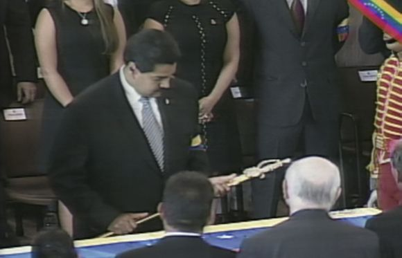 TV grab shows Vice President Nicolas Maduro holding a replica of the Simon Bolivar's sword as he stands over the coffin of Hugo Chavez, during the funeral at the military academy in Caracas.