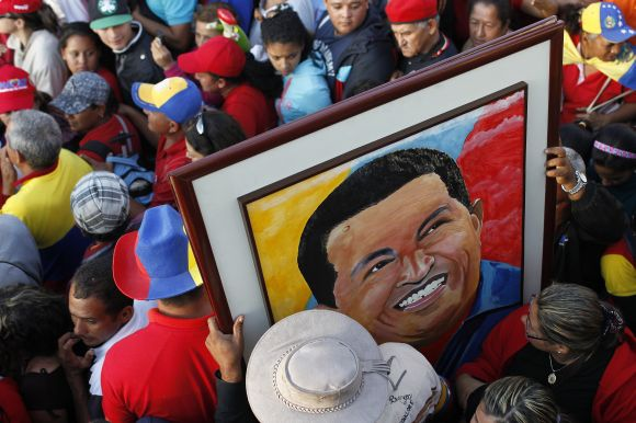 Supporters of Hugo Chavez hold a portrait of him near the military academy in Caracas on Friday