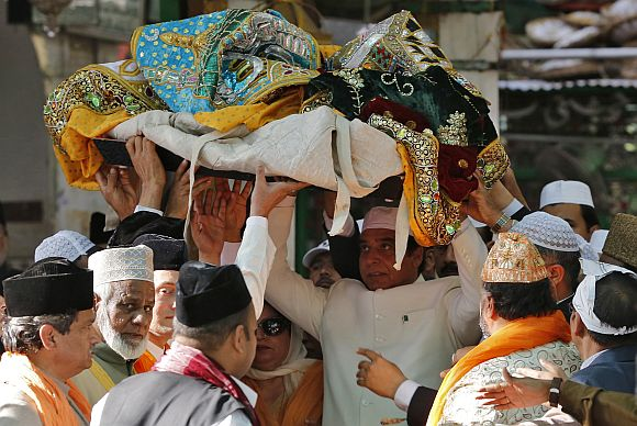 Pakistan's Prime Minister Raja Pervez Ashraf (C) carries an offering at the shrine of Sufi saint Khwaja Moinuddin Chishti at Ajmer
