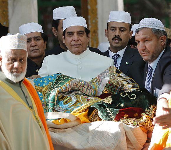 Pakistan's Prime Minister Raja Pervez Ashraf (C) carries an offering at the shrine of Sufi saint Khwaja Moinuddin Chishti at Ajmer