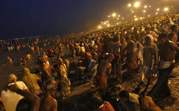 Hindu devotees gather to take a holy dip in the waters of the river Ganges during the early morning on the last bathing day of Kumbh Mela in Allahabad