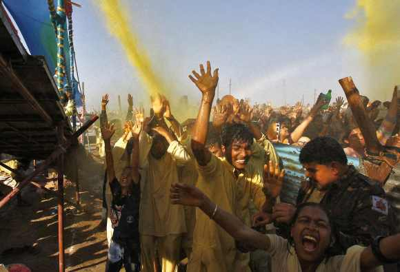 Devotees raise their hands to receive coloured holy water from a priest at the Kumbh Mela