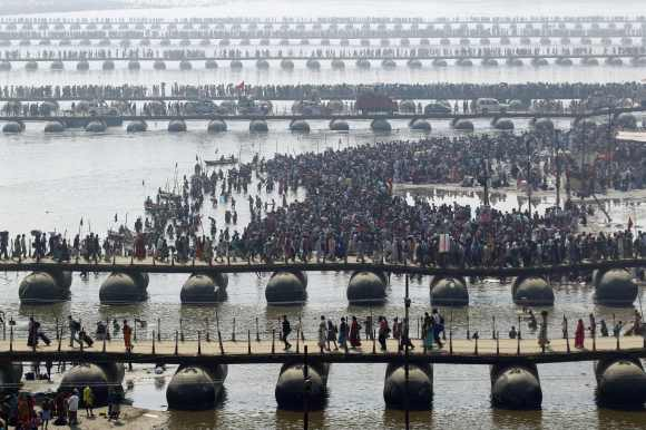 Devotees cross the river Ganges on pontoon bridges after bathing in the waters at Sangam