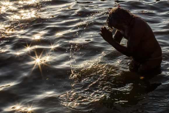 A devotee bathe on the banks of Sangam