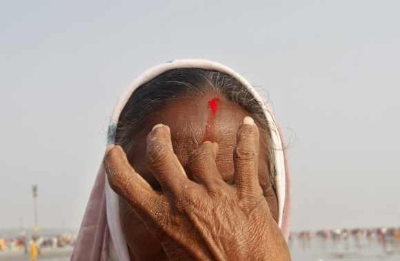 A femalA Hindu pilgrim receives a 'sindur' mark on her head after taking a dip at the confluence of the Ganga