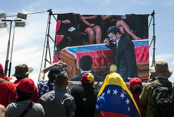 Supporters of Hugo Chavez watch a screen as Mahmoud Ahmadinejad walks past Chavez's coffin during the funeral ceremony