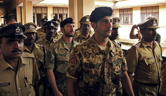 File photo shows Salvatore Girone (C) and Latorre Massimiliano (3rd R), members of the navy security team of Napoli registered Italian merchant vessel Enrica Lexie, being escorted as they leave a courtroom at Kollam, Kerala