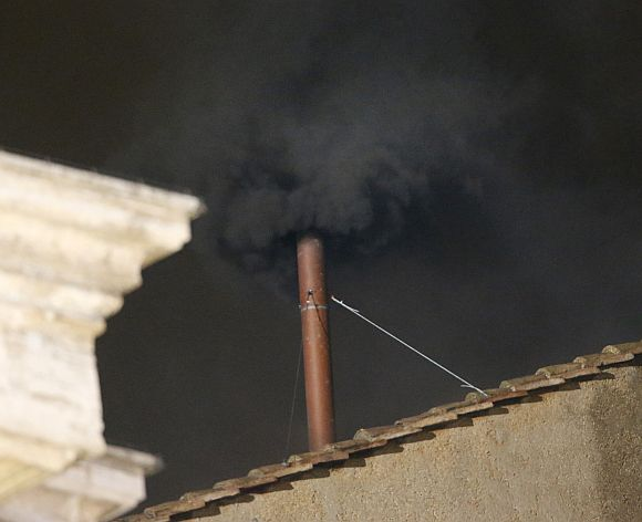 Black smoke rises from the chimney on the roof of the Sistine Chapel in the Vatican City indicating that no decision has been made after the first day of voting for the election of a new pope