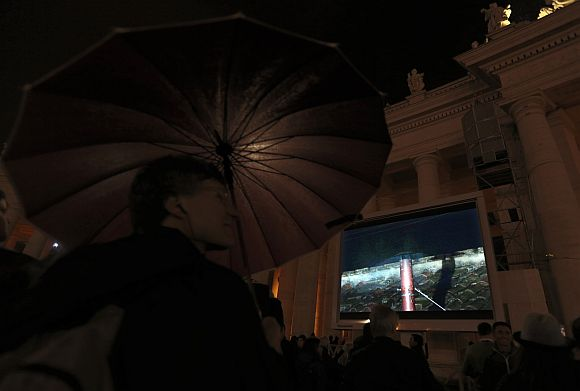 People in Saint Peter's Square watch a live television screen showing black smoke rising from the chimney above the Sistine Chapel, indicating that no decision has been made after the first day of voting