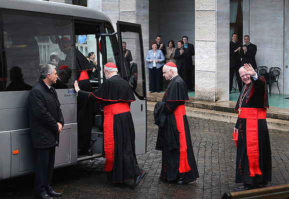 American Cardinals (left to right) Sean P O'Malley, Keith O'Brien and Timothy M Dolan board a bus to take them from the North American College to St Peter's Basilica where a Pro Eligendo Romano Pontifice Mass will be celebrated before they ente