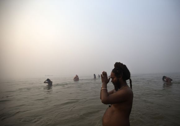 A Sadhu prays as he takes a dip during the first Shahi Snan at Kumbh Mela in Allahabad