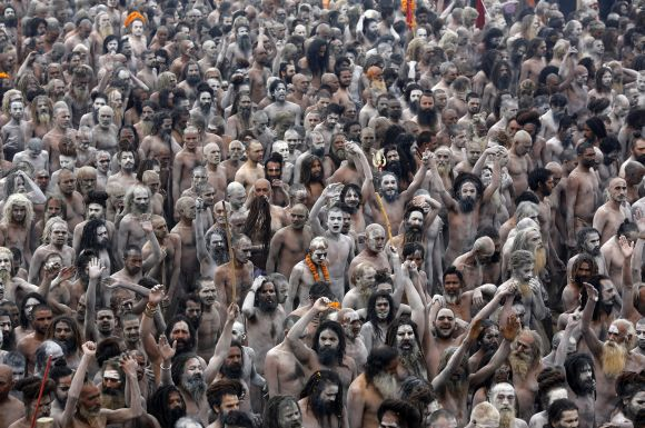 Naga Sadhus raise their arms while shouting religious hymns on the banks of Ganga after taking the holy dip at Kumbh Mela in Allahabad.