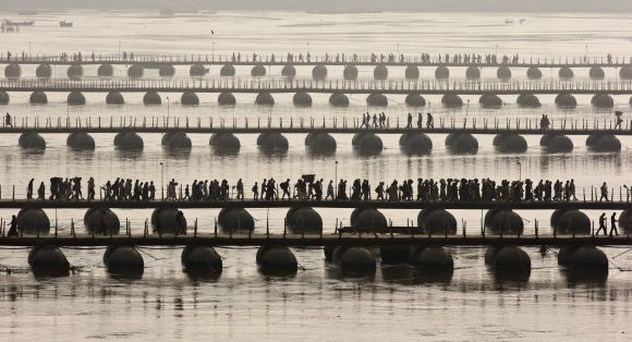 Devotees cross pontoon bridges spanning the river Ganga during the a 'Shahi Snan' at the Kumbh Mela.