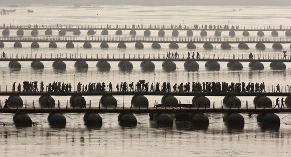 Devotees cross pontoon bridges spanning the river Ganga during the a 'Shahi Snan' at the Kumbh Mela.