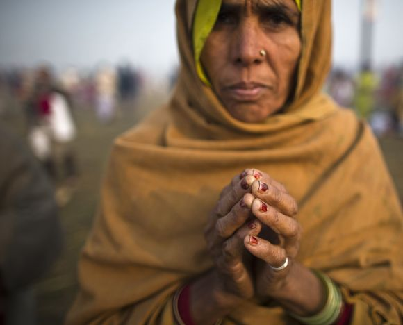 A devotee gestures after bathing in Ganga during the Kumbh Mela.