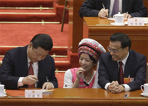China's Vice-Premier Li Keqiang and an ethnic minority delegate look at Xi Jinping signing an autograph for the delegate during the fourth plenary meeting of National People's Congress