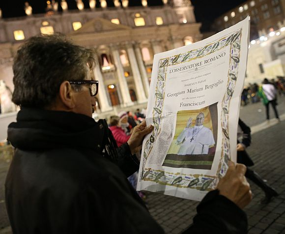 A man reads a special edition of L'Osservatore Romano newspaper which carries a photograph of newly elected Pope Francis I on