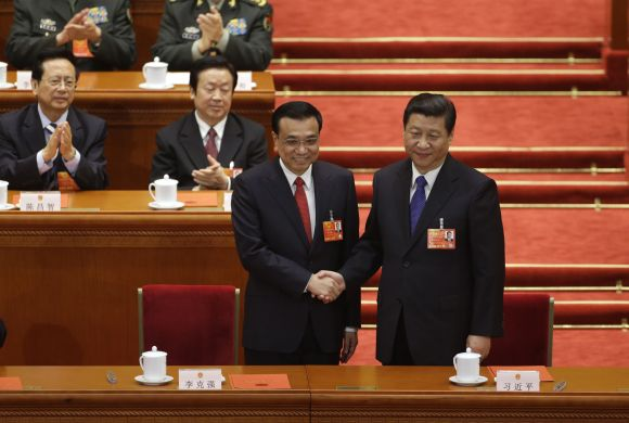 China's President Xi Jinping (R) shakes hands with China's newly-elected Premier Li Keqiang during the fifth plenary meeting of the National People's Congress (NPC) at the Great Hall of the People in Beijing