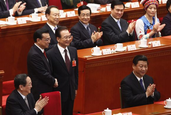 China's newly-elected Premier Li Keqiang shakes hands with China's former Premier Wen Jiabao (front, 3rd L) as China's President Xi Jinping (front, R) and other delegates clap during the fifth plenary meeting of the National People's Congress at the Great Hall of the People in Beijing.