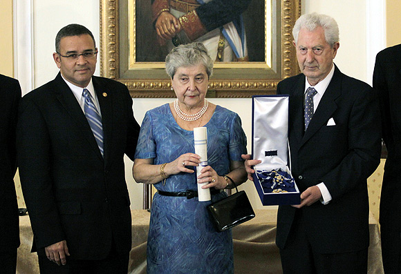 El Salvador's President Mauricio Funes (left) presents a medal to Juan Antonio Ellacuria, brother of Spanish-born Jesuit priest Ignacio Ellacuria, and his wife Manuela Balenciaga, on the 20th anniversary of his brother's murder, in San Salvador, November 16, 2009.