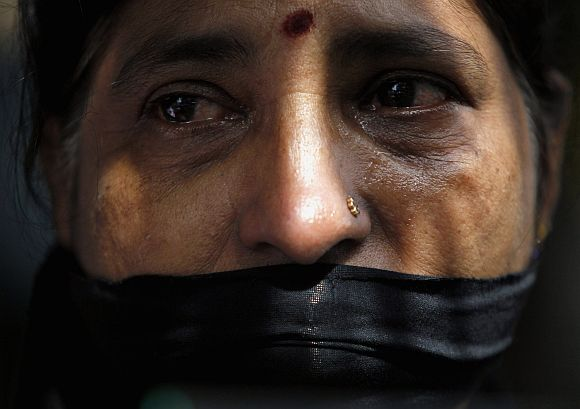 A Tamil woman cries next to an image of a missing family member as she wears a black cloth across her face during a protest in front of Parliament in Colombo. The protest was held to mark 3 years since the disappearance of Prageeth Eknaligoda who worked for Lanka-e-News, a privately owned independent network that was critical of the government.
