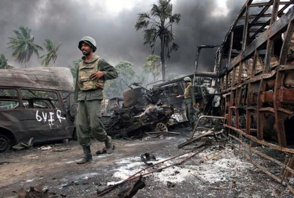 File photo shows Sri Lankan troops walking near burnt or burning vehicles in the area inside the war zone near the town of Mullaittivu
