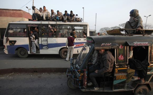 A vendor tries to sell bananas to the passengers sitting atop of a bus as they wait to cross a toll gate at Hajipur industrial park on the outskirts of the eastern Indian city of Patna, in Bihar