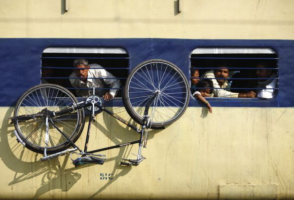 A bicycle hangs from the window of a train at Parsha Bazar railway station in Bihar