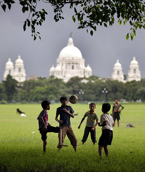Children play soccer against the backdrop of the Victoria Memorial in Kolkata built as a tribute to Queen Victoria in the early 20th century.