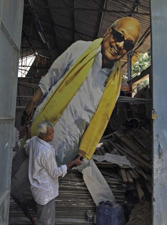 A man carries a poster of DMK chief M Karunanidhi