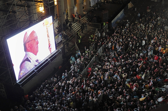 Faithful watch the inaugural mass of Pope Francis on a giant screen next to the Metropolitan Cathedral in Buenos Aires.