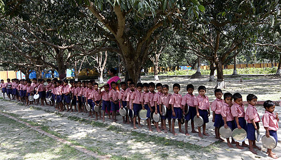 Children queue up to collect their free mid-day meal distributed by a non-governmental organisation inside a school in Kolkata.