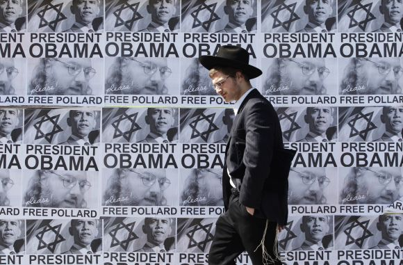An ultra-Orthodox Jewish man walks past posters calling for US President Barack Obama to free Jonathan Pollard from a US prison, in Jerusalem. Pollard, a former US Navy intelligence analyst, has been serving a life sentence in the United States since he was caught spying for Israel in the 1980s.