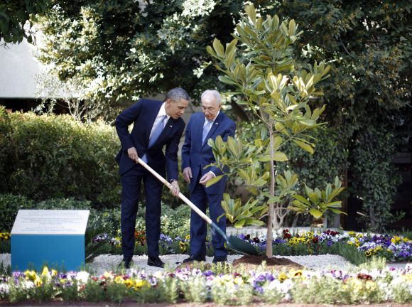 US President Barack Obama participates in the planting of a magnolia tree from the White House, at the residence of Israel's President Shimon Peres in Jerusalem.