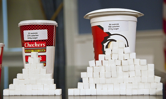 Soft drink cups sized (left to right) at 32 ounces and 64 ounces are displayed at a news conference at City Hall in New York. Under a new law proposed by New York City Mayor Michael Bloomberg, all soft drinks over