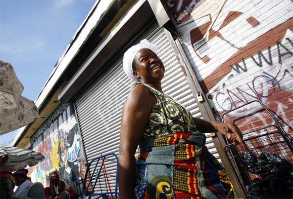 A Liberian woman walks on a sidewalk market outside a housing project in the Park Hill section of Staten Island in New York