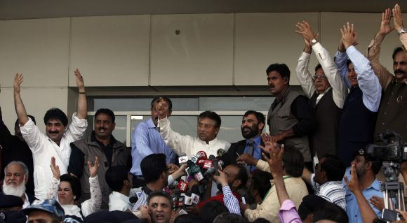 Musharraf gestures to his supporters upon his arrival at Karachi airport