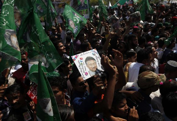 Supporters of Pervez Musharraf carry flags and portraits of their leader as they wait upon his arrival in Karachi
