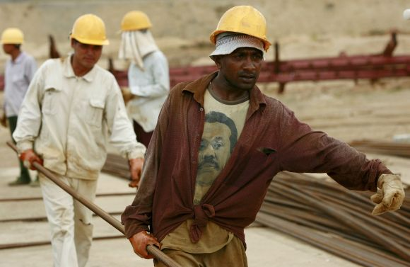 A Sri Lankan worker carries an iron bar with Chinese workers at the construction site for the now operational shipping port in Hambantota.