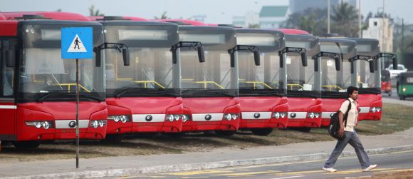 A man walks past China-made buses in Colombo
