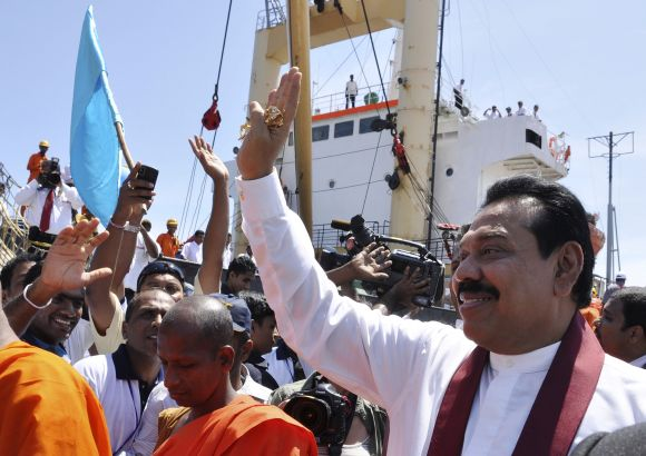 Sri Lanka's President Mahinda Rajapaksa waves at the crowd after the first ship docked at the port in Hambantota.