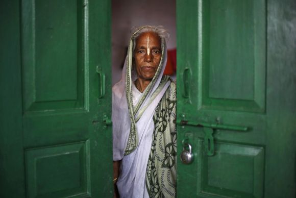 A widow poses for a picture inside her room at the Meera Sahavagini ashram in Vrindavan