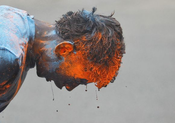 A schoolboy reacts after coloured powder was thrown on him by an another schoolboy during Holi celebrations in Ahmedabad