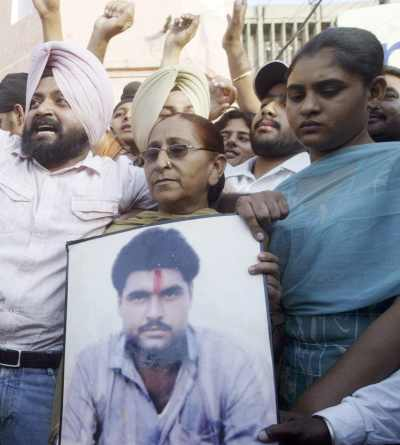 Family members of Sarabjit Singh hold his picture